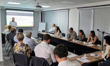 Imagem Dos Membros Do Conselho Estratégico Sentados Em Uma Mesa única Em Formato De U. Os Participantes Estão Direcionados Para Um Telão Que Contém A Apresentação Do Tema Da Reunião
