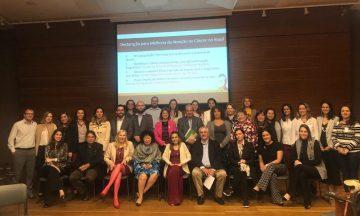 A Imagem Contém A Foto De Todos Os Participantes Da Reunião Dos Grupos De Trabalho Que Estão Juntos, Lado A Lado, E Atrás Deles O Telão Do Projetor Com A Apresentação Do Tema Da Reunião