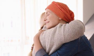 A Imagem Contém Uma Foto Da Uma Mulher Com Um Lenço Na Cabeça, Que Está Sorrindo Enquanto Abraça Outra Pessoa. O Objetivo Da Imagem é Representar A Boa Notícia, De Que O Bussulfano Está Garantido Até 2022.