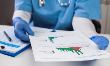 Imagem De Um Profissional Da Saúde, Segurando Com Luvas, Um Papel Que Contém Gráficos E Dados De Uma Pesquisa, Referente Ao COVID-19.