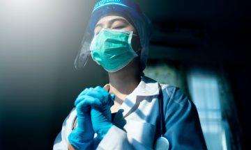 Imagem De Uma Mulher Profissional Da Saúde, Toda Equipada Com Máscara, Luvas E Protetor Facial. A Profissional Está Com Os Olhos Fechados E As Mãos Em Posição De Suplica, Representando O Pedido De Socorro Ao Mundo.