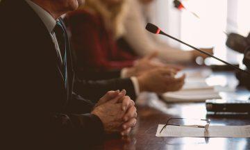 Imagem De Perfil De Três Pessoas Próximas à Um Microfone, Discutindo Sobre Um Tema, Em Representação Ao Debate Da Comissão Sobre Detecção Precoce E Controle Do Câncer No SUS.