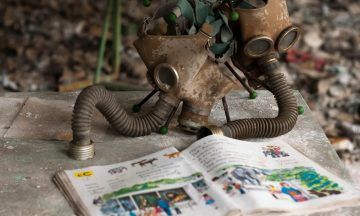 Imagem De Duas Máscaras Respiratórias Antigas Que Estão Perto De Um Livro, No Qual Representa A História Do Acidente De Chernobyl
