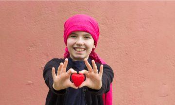 Imagem De Uma Criança Com Um Laço Na Cabeça, Sorrindo E Segurando Um Objeto Em Formato De Coração