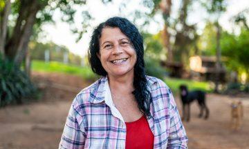Imagem De Uma Mulher Sorrindo, Em Representação à Saúde Da Mulher, E Ao Fundo Uma Paisagem De Campos Verdes, árvores, Casa E Cachorros.