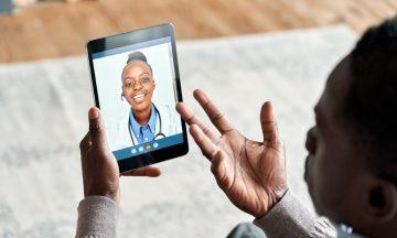Imagem De Um Homem Em Casa Segurando Um Tablet Nas Mãos, Em Chamada Online Com Uma Médica.