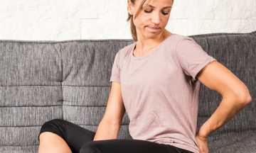 Imagem De Uma Mulher Com Roupas Esportivas, Sentada Em Um Sofá . A Mulher Tem Uma Expressão Facial De Incerteza, Em Representação Ao Título Da Pesquisa, Pandemia, Ansiedade, Atividade Física E Câncer De Mama: Há Uma Correlação?