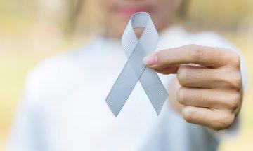 Imagem Desfocada Uma Mulher Ao Fundo, Segurando Um Laço Com A For Da Campanha Maio Cinza, Mês Do Câncer De Cérebro