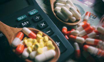 Imagem De Pílulas Medicativas Em Uma Superfície Plana, Alguns Aglomeradas Em Duas Colheres De Madeira Que Estão Próximas à Uma Calculadora Em Representação à Isenção De Impostos Aos Medicamentos Que Tratam O Câncer