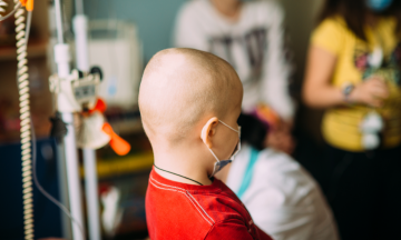 Imagem De Uma Criança, Paciente De Câncer, De Costas Junto De Outras Pessoas Em Uma Sala No Hospital