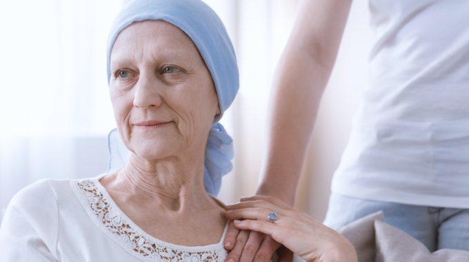 Imagem De Uma Mulher Idosa Com Câncer, Apresenta Um Lenço Na Cabeça, E Está Segurando A Mão De Outra Pessoas Que A Conforta
