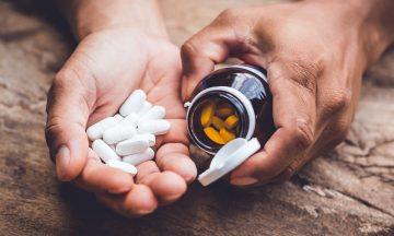 Imagem De Uma Vários Pílulas Orais Sem Uma Mão E Em Outra O Frasco Do Medicamento