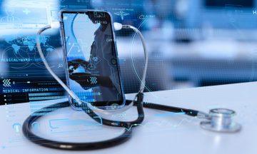 Imagem De Um Celular Com Um Estetoscópio Em Volta, Em Representação Ao Aplicativo Criado Para Monitoramento Do Câncer