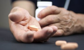 Imagem De Uma Mão Apoiada Em Uma Superfície Segurando Medicamentos Orais E A Outra O Frasco Dos Medicamentos